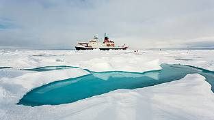 The German research icebreaker has stopped next to an big Arctic ice floe. In the foreground one can see one of the many melt ponds, which cover the Arctic sea ice in summer.