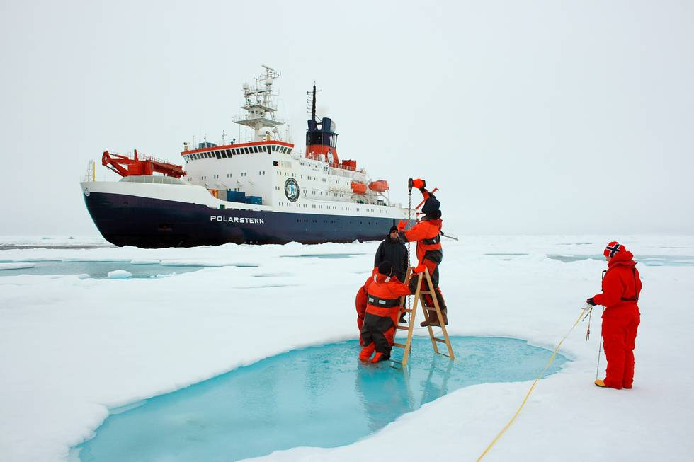 AWI sea-ice physicists drill a hole to measure the exact thickness of the arctic sea ice they are working on.