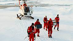 AWI scientists unload the Polarstern helicopter, which had help them to reach an ice float for intensive investigations and measurements.