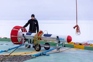 Scientists preparing the EM-Bird, an instrument towed by helicopters to measure thickness of sea ice.