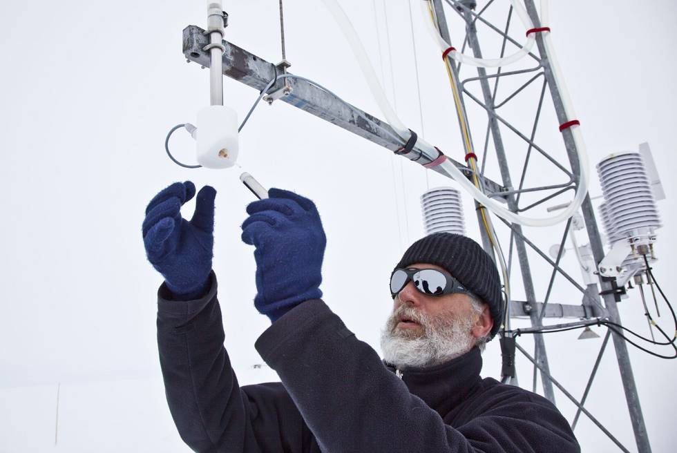 Meteorologist Jölund Asseng, member of the overwinterer team (2011), is doing some maintenance work at the Met tower at Neumayer-Station III, Antarctic.