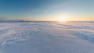 Schneebedecktes arktisches Meereis bei Sonnenuntergang