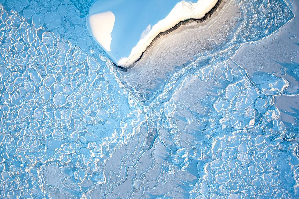Antarctica: An iceberg drifts through so called pancake ice in the Weddell Sea. The remarkably-shaped ice pads are an early stage of evolving sea ice. Wave motions cause their shape.