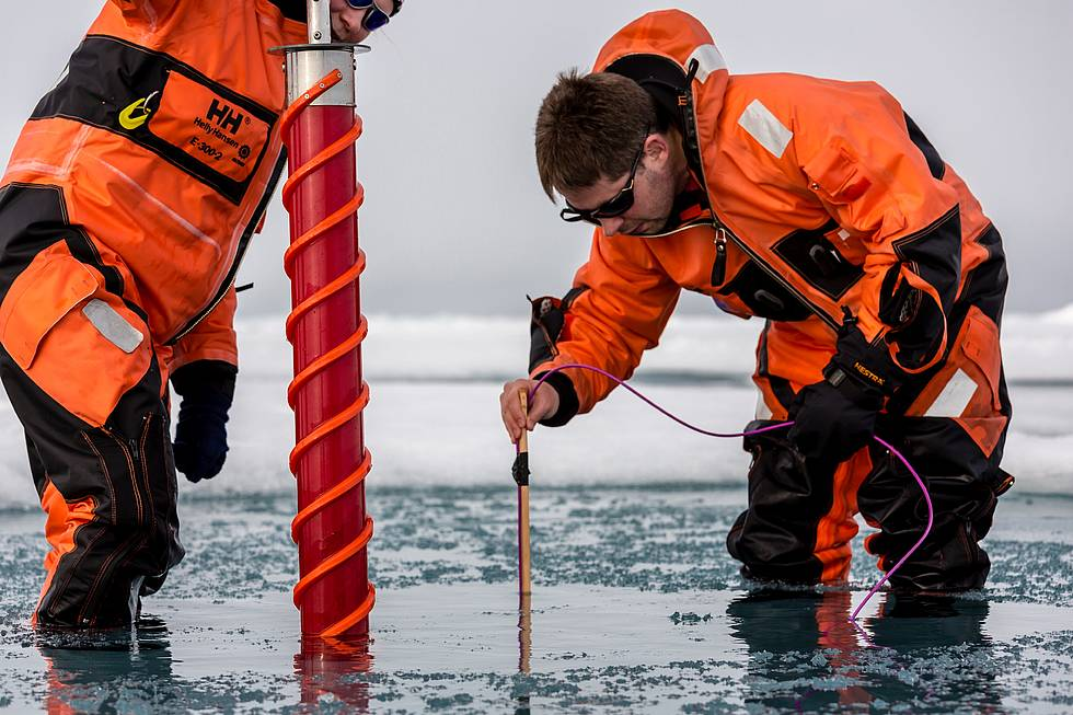 Through a drill hole AWI sea-ice physicist Marcel Nicolaus is investigating the sea ice underneath the melt pond, he and his colleague are standing in.