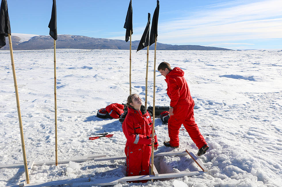 AWI scientist Janin Schaffer and a coworker build an ice radar measurements station for the AWI glaciologists on the floating tongue of the 79° North Glacier.