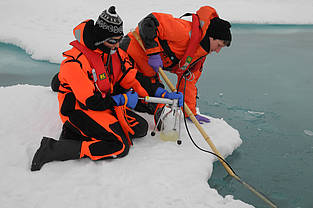 AWI biologist Ilka Peeken (r) is focusing her research on ice algae. This image shows her and a colleague during investigations of a melt pond on Arctic sea ice.