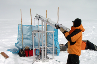 A member of DRI's ice core research team extracts an ice core from the Greenland Ice Sheet.