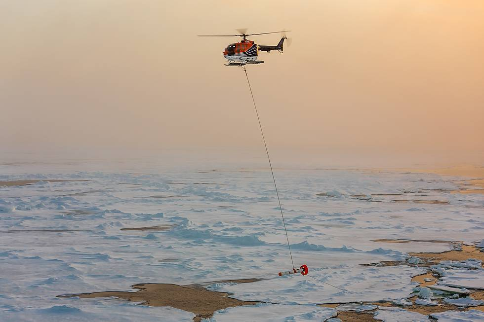 One of the two Polarstern helicopters is carrying the AWI sea-ice thickness sensor EM-Bird across the arctic sea-ice cover.