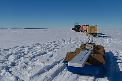 Towing the GEM sea ice thickness sensor on a blue sledge behind a snow scooter and 2 Nansen sledges across the sea ice of Atka Bay