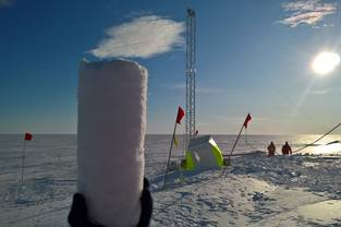 One of the first pieces of shallow ice-core drilled by the new system in the backround. Close to Gwerman Antarctic Neumayer Station III